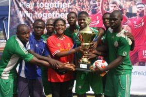 Mrs Yetunde Oni, Head Commercial Clients, Standard Chartered Bank (3rd left), presenting the Trophy to Captain of Super Seven Football Club, Ojo Babatunde Damilola, the winner of the just concluded Standard Chartered Road to Anfield 2015 competition.